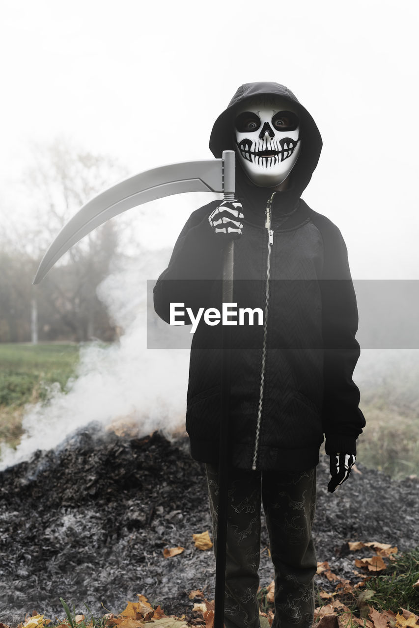Portrait of person wearing costume standing against smoke at park