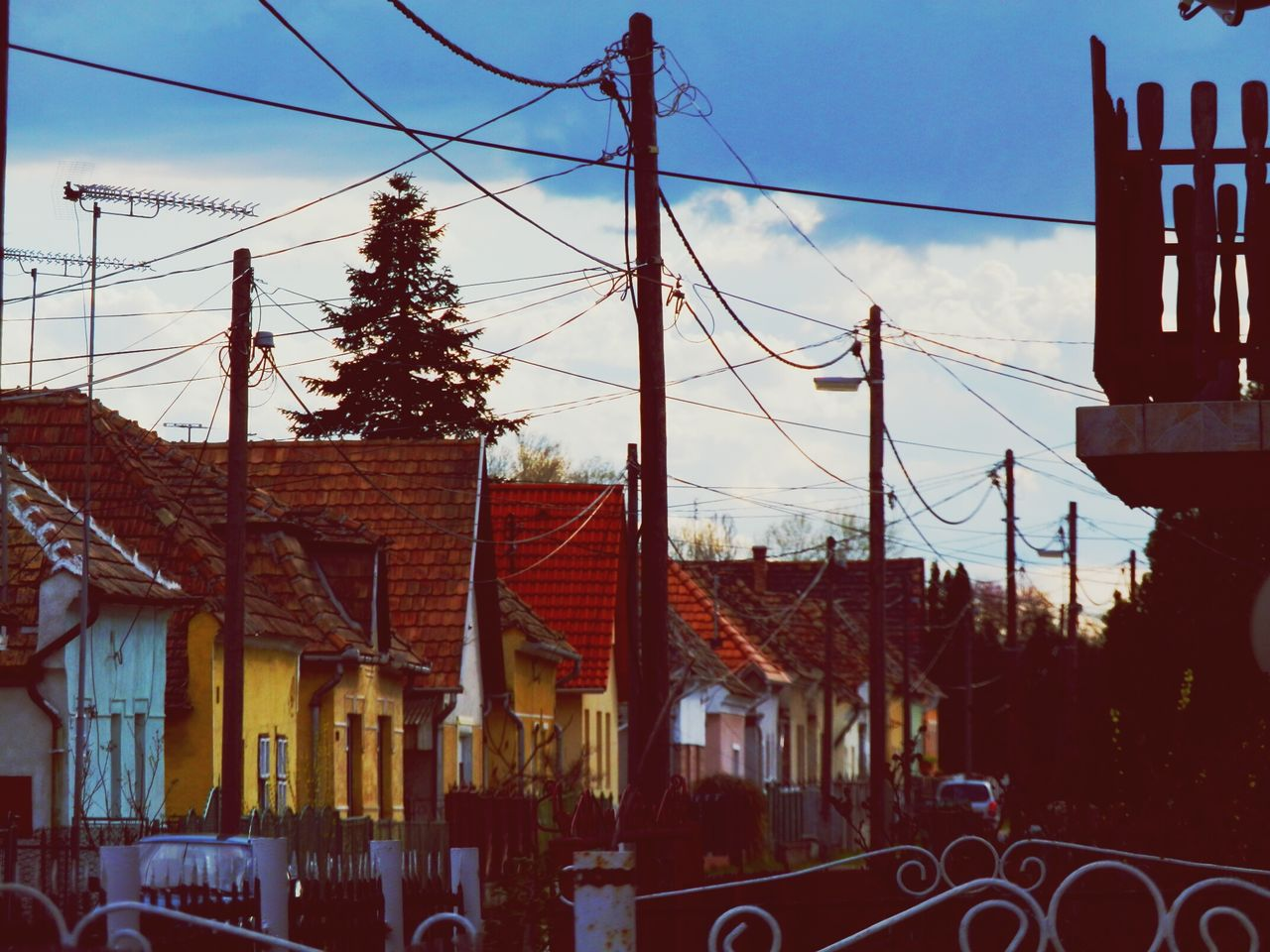 Low Angle View Of Wire And Pole By Houses Against Cloudy Sky