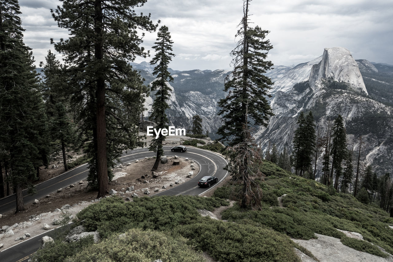 High Angle View Of Winding Road In Forest Against Mountains