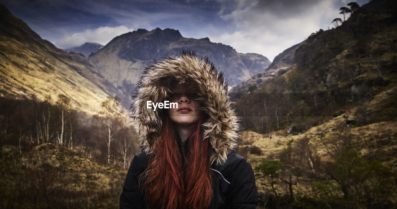 Smiling Young Woman Wearing Hooded Jacket Against Snow Covered Mountains
