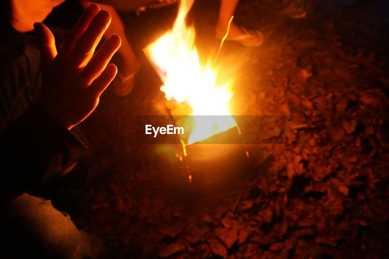 fire, burning, heat - temperature, flame, fire - natural phenomenon, human hand, hand, nature, one person, glowing, real people, human body part, motion, night, holding, log, orange color, wood, bonfire, finger, outdoors, dark, campfire