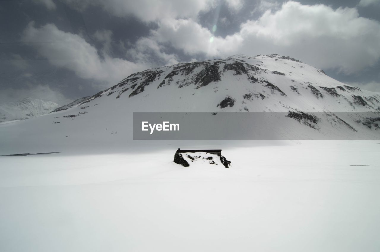 HELICOPTER ON SNOW COVERED MOUNTAIN AGAINST SKY