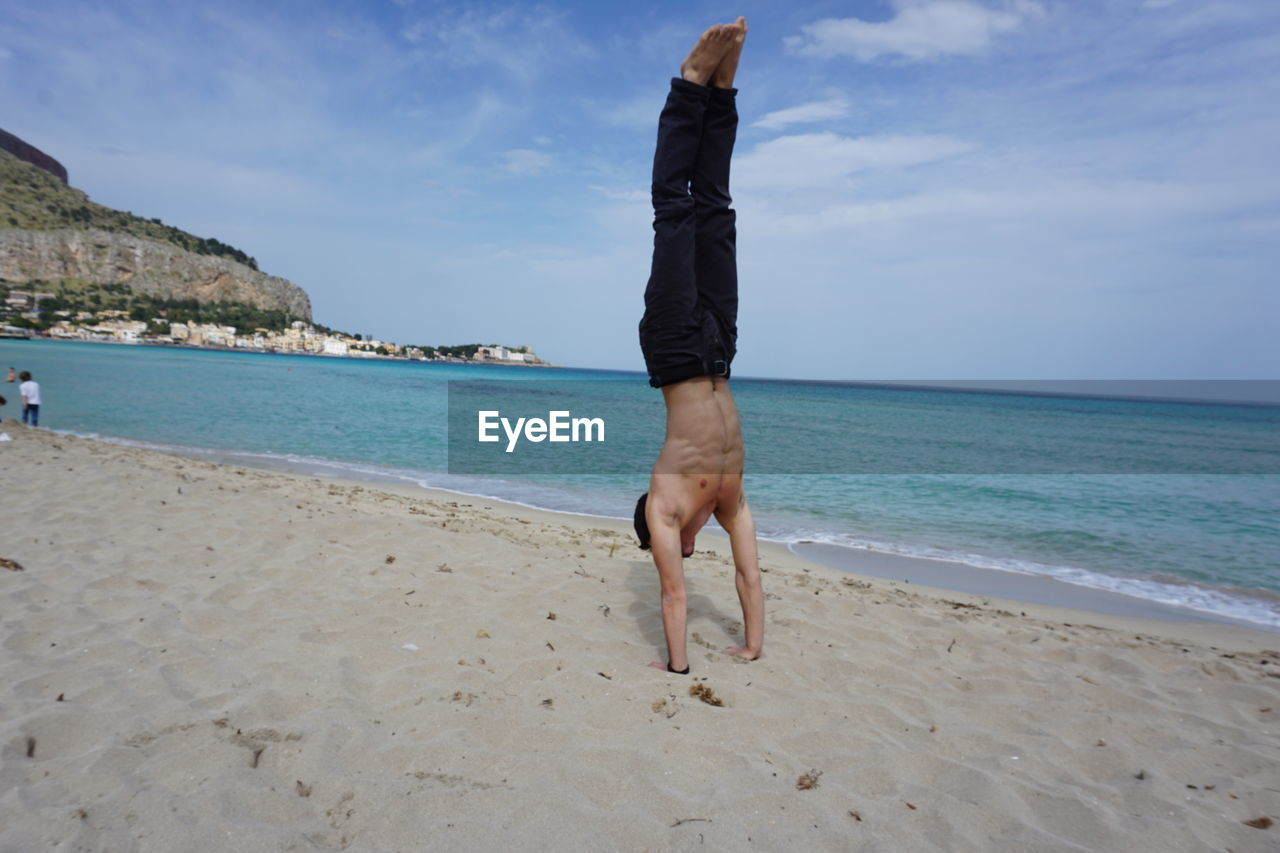 Full Length Of Shirtless Man Doing Handstand On Sand At Beach Against Sky