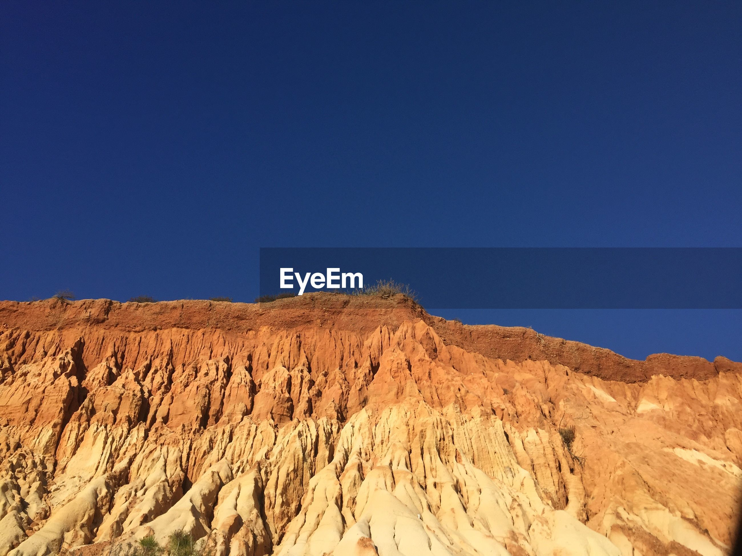 LOW ANGLE VIEW OF BARREN LANDSCAPE AGAINST CLEAR BLUE SKY