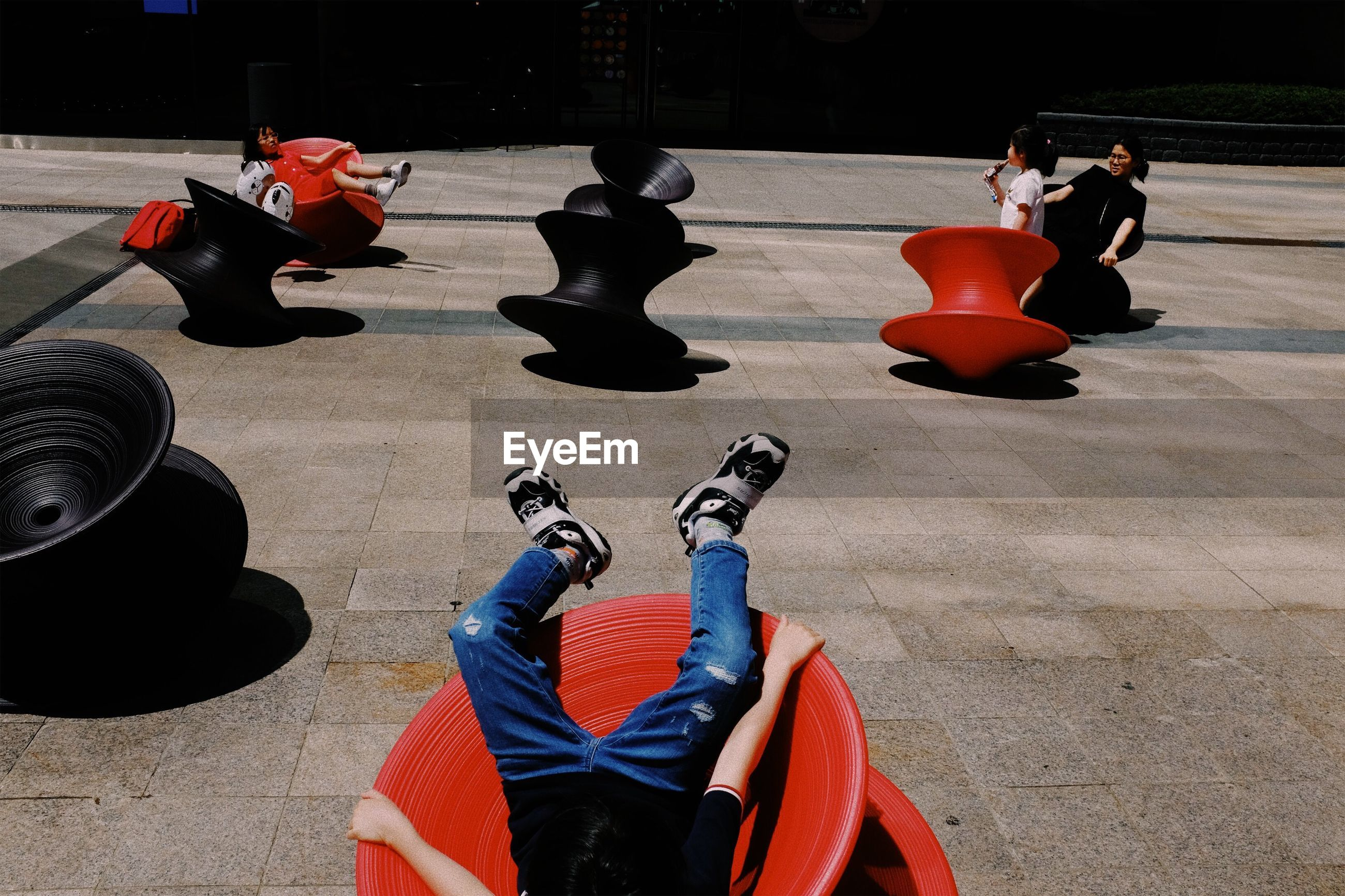 red, day, real people, people, high angle view, sunlight, human body part, body part, group of people, sitting, lifestyles, unrecognizable person, men, outdoors, representation, relaxation, leisure activity, flooring, black color, shadow