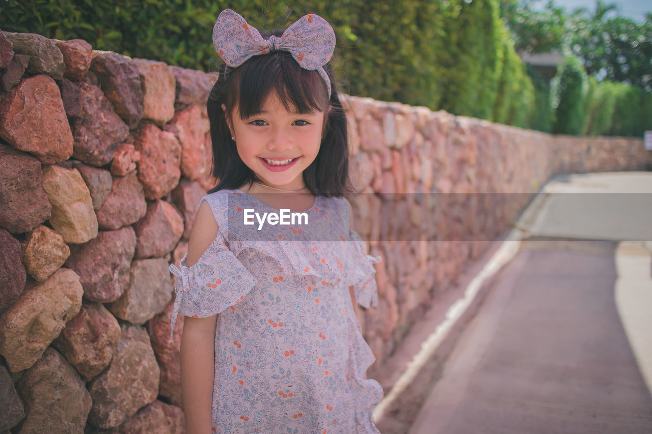 Portrait of smiling girl wearing headband standing against stone wall