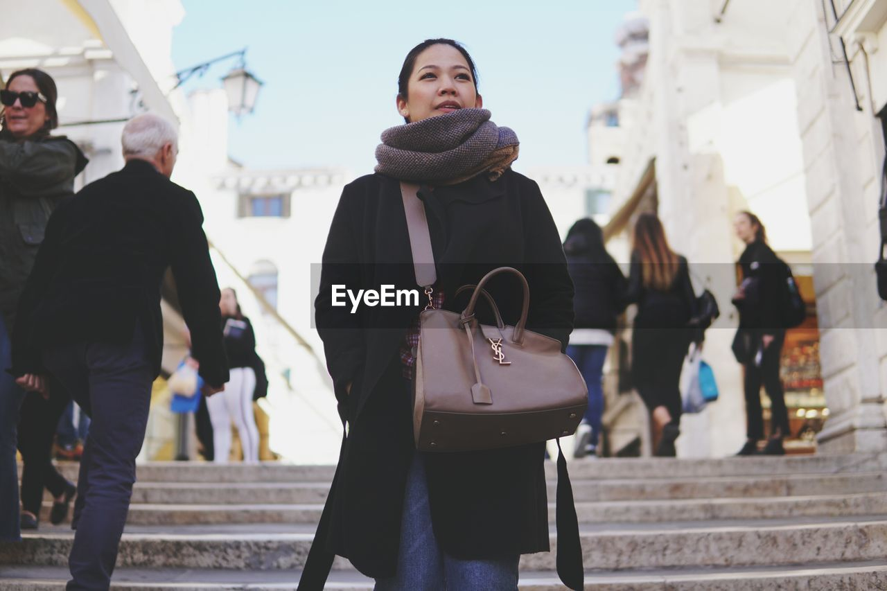 real people, adult, city, women, architecture, incidental people, lifestyles, men, focus on foreground, leisure activity, people, three quarter length, day, standing, clothing, casual clothing, walking, group of people, young adult, emotion, outdoors, warm clothing