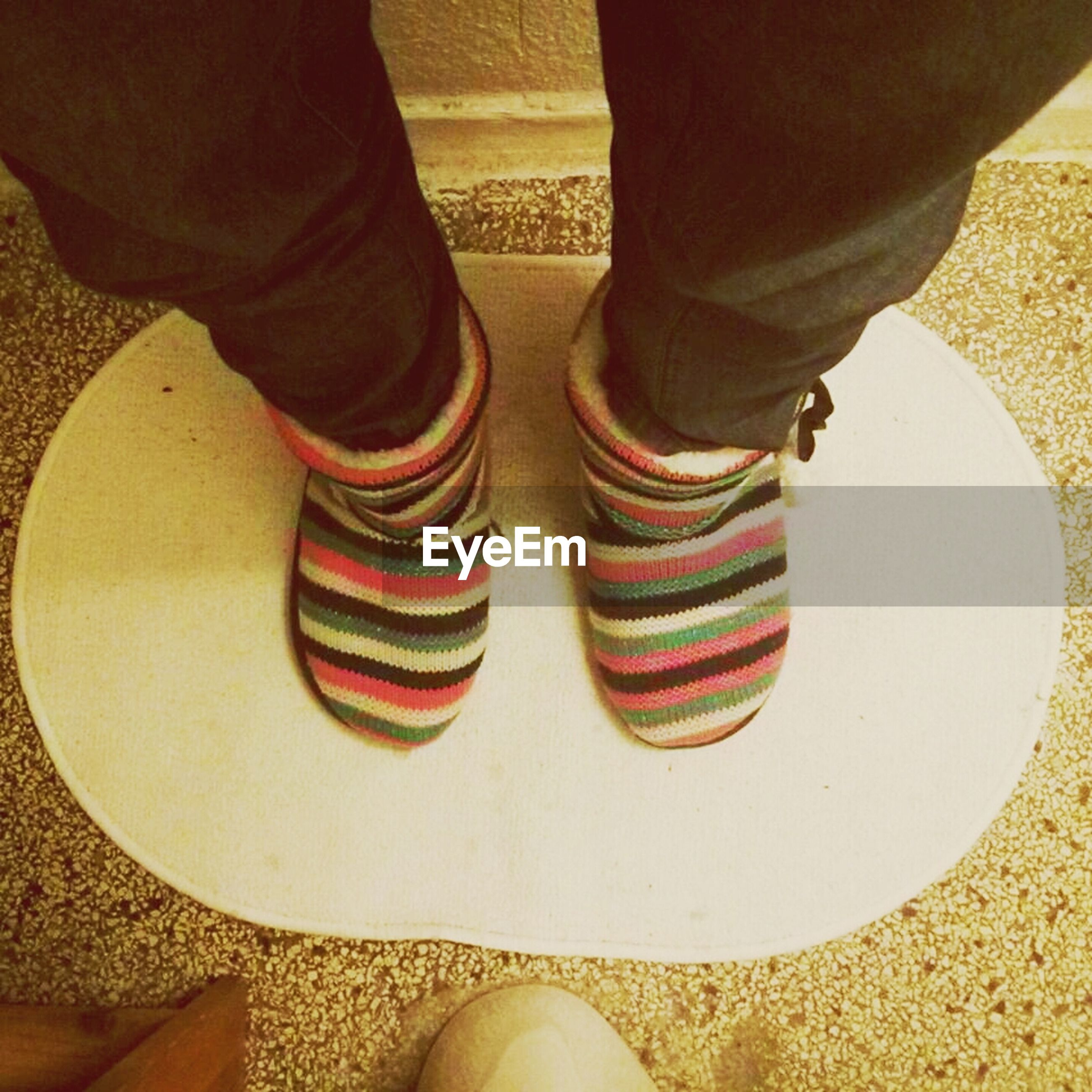low section, person, shoe, standing, lifestyles, human foot, indoors, footwear, men, leisure activity, casual clothing, jeans, flooring, high angle view, togetherness