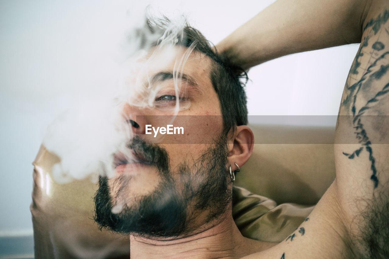 Close-Up Of Tattooed Man Smoking