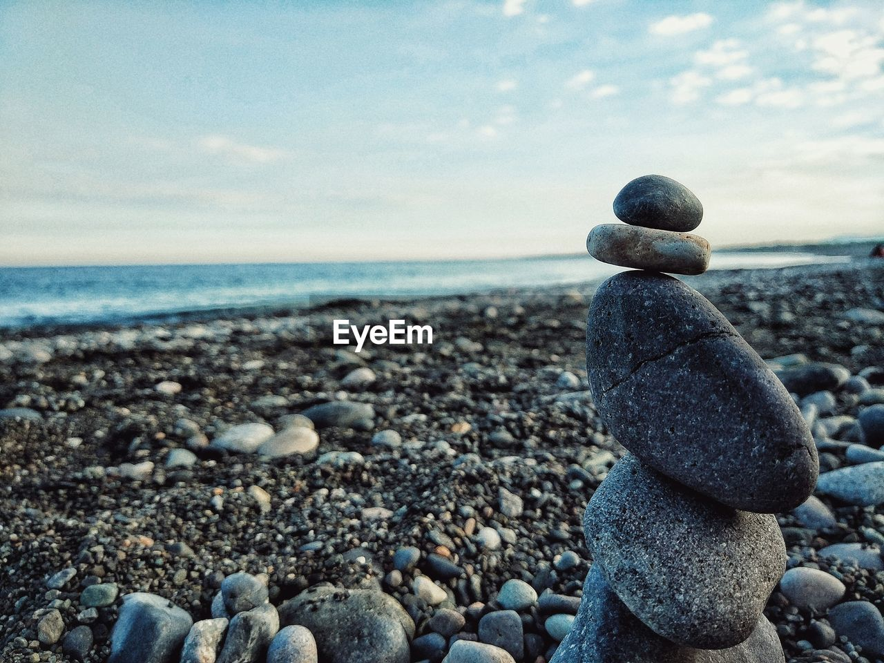 Stack of stone at beach against sky