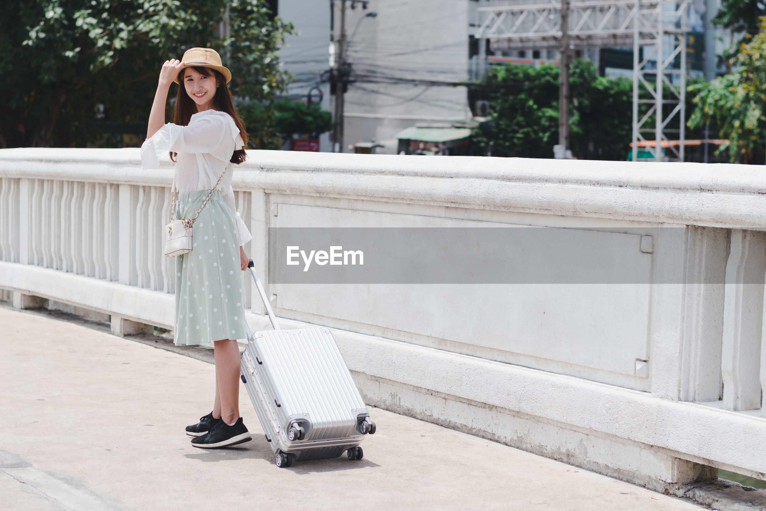 Full length portrait of smiling young woman holding luggage while standing on road