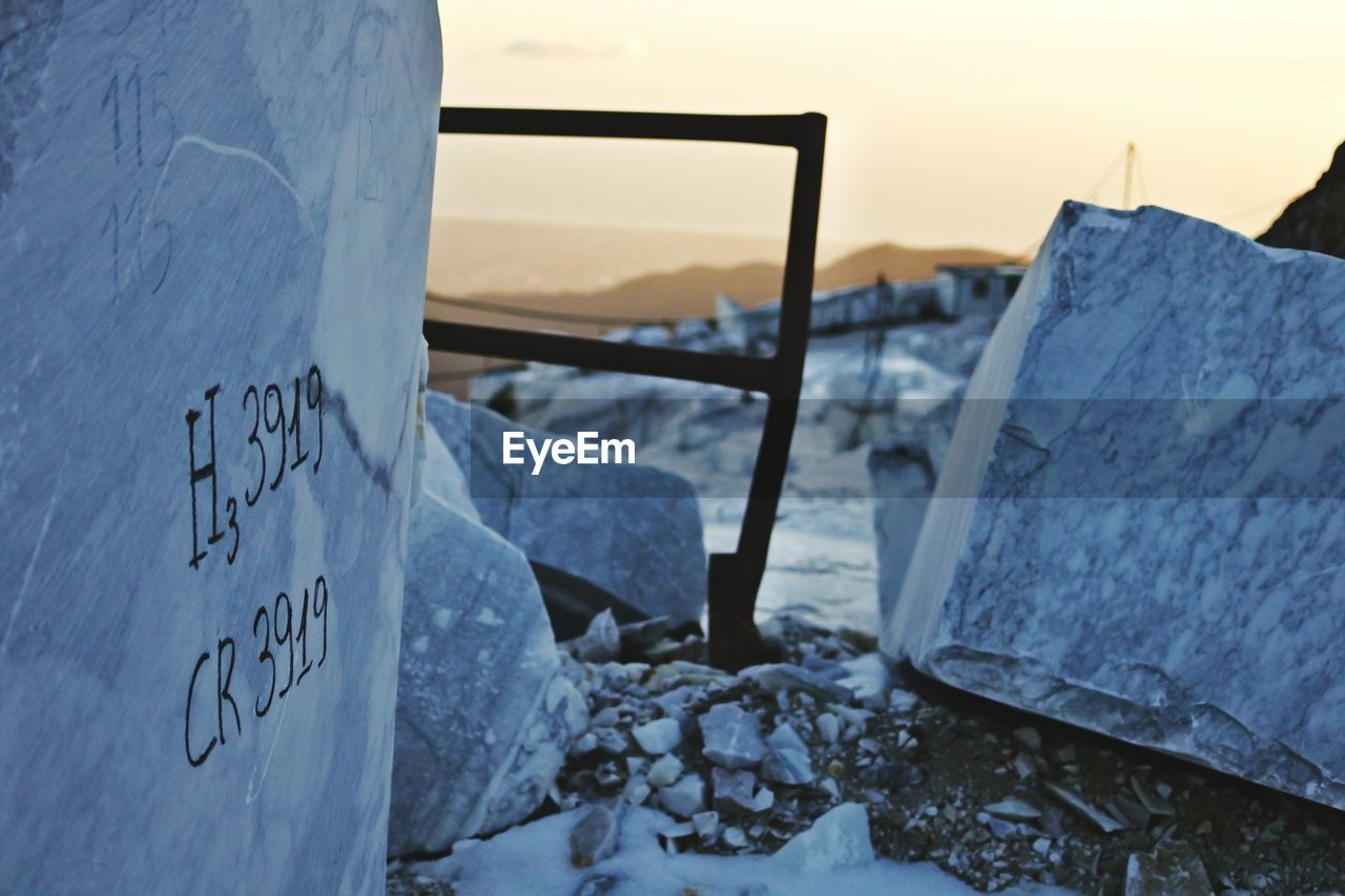 CLOSE-UP OF TEXT ON SNOW COVERED ROCKS AGAINST SKY