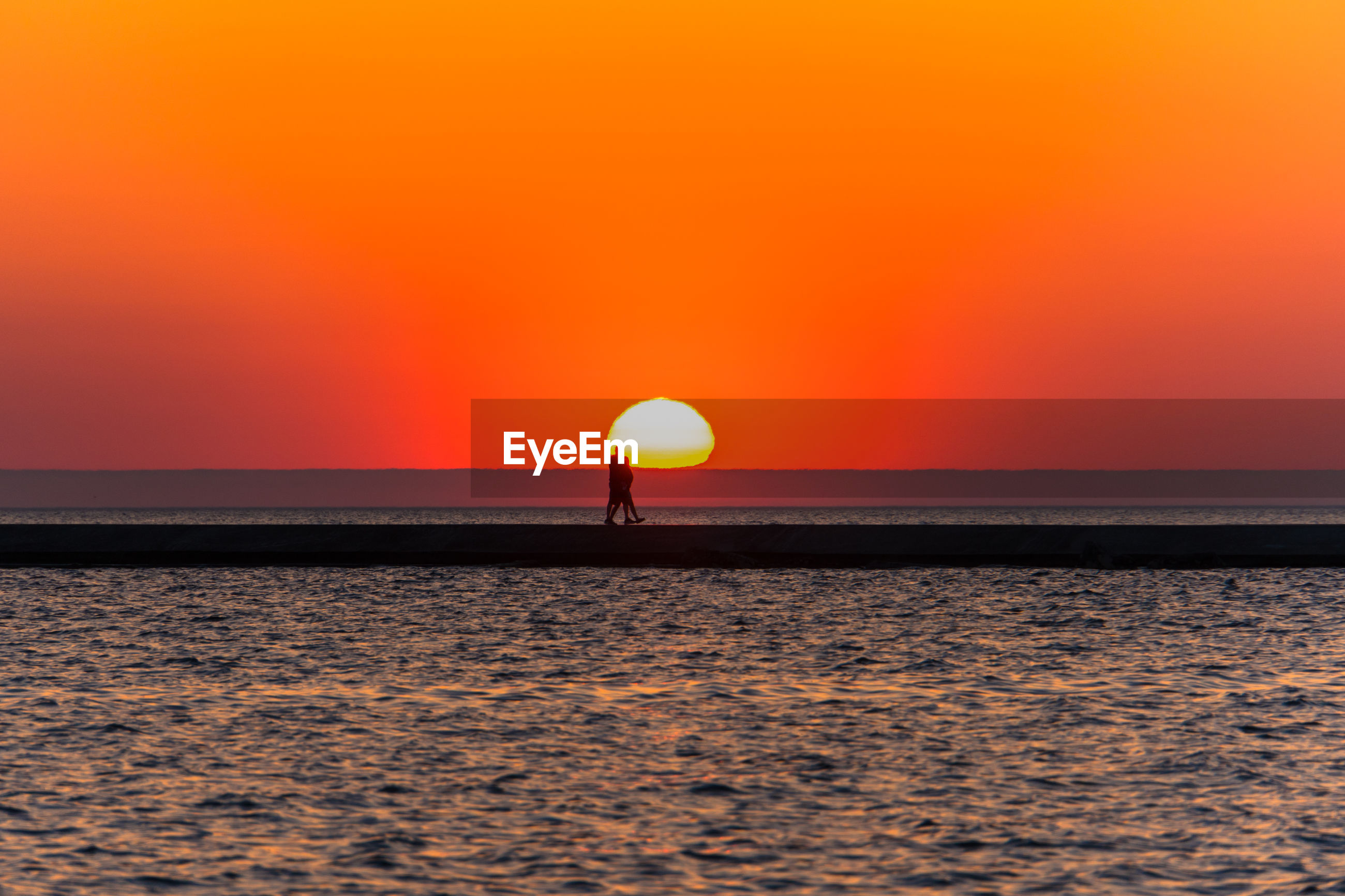 SILHOUETTE SEA AGAINST ORANGE SKY