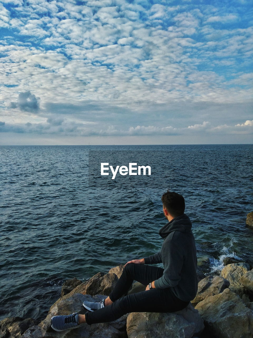 sea, water, one person, sitting, real people, leisure activity, beauty in nature, lifestyles, scenics - nature, sky, horizon, horizon over water, rock, rock - object, solid, cloud - sky, nature, relaxation, tranquility, outdoors, looking at view