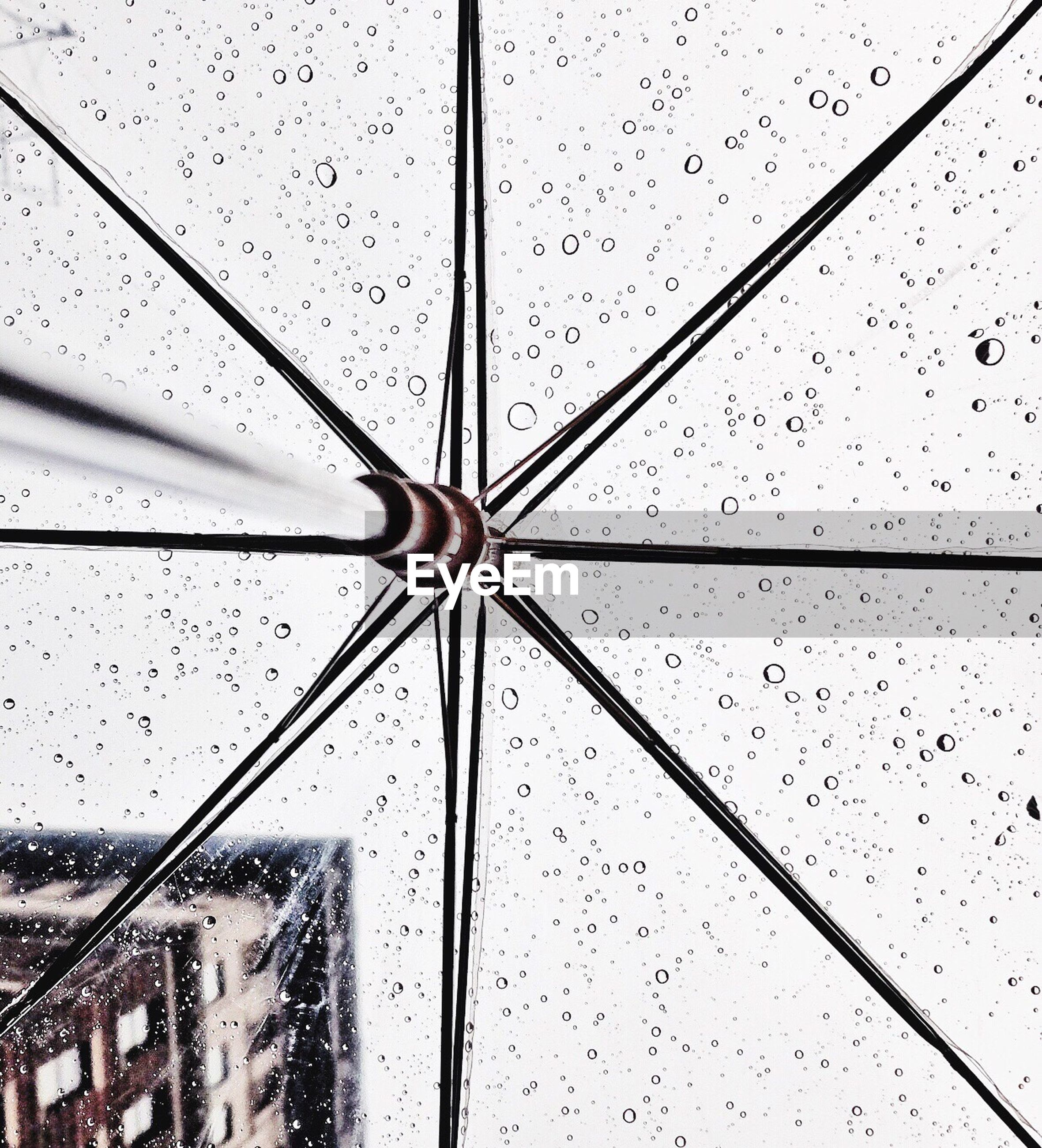 Low angle view of wet transparent umbrella against sky during monsoon