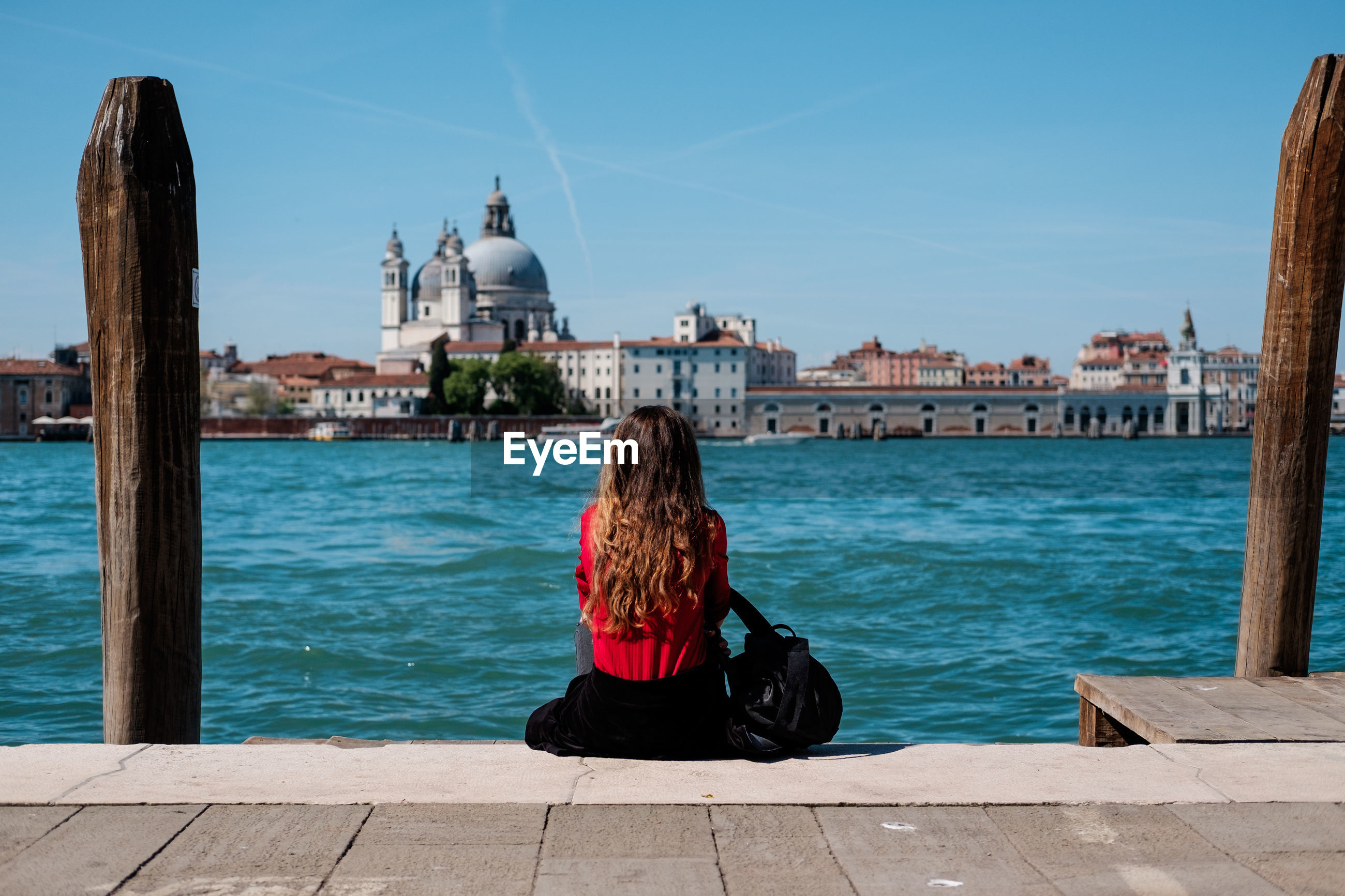 Rear view of woman sitting on pier at grand canal in old town
