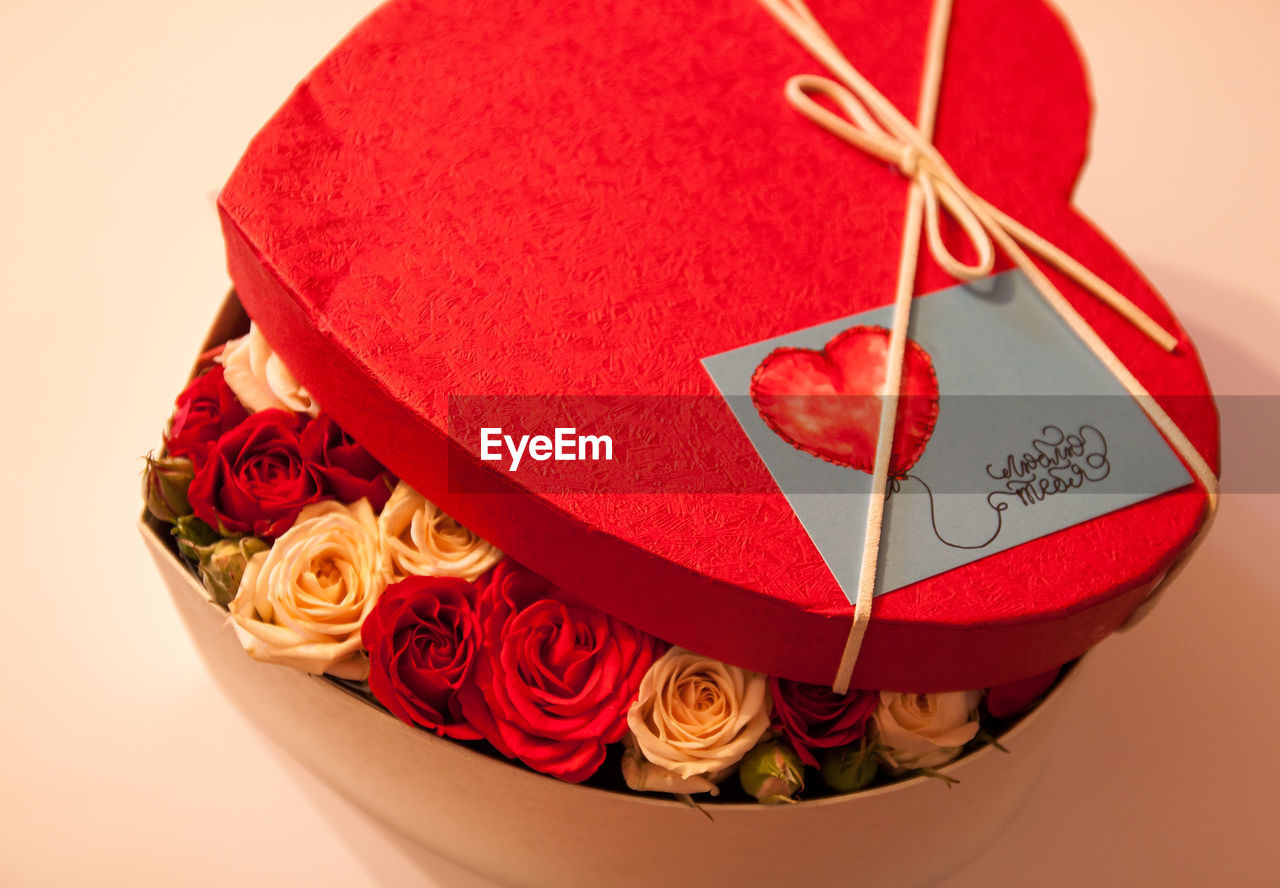 High angle view of roses in heart shape box on table