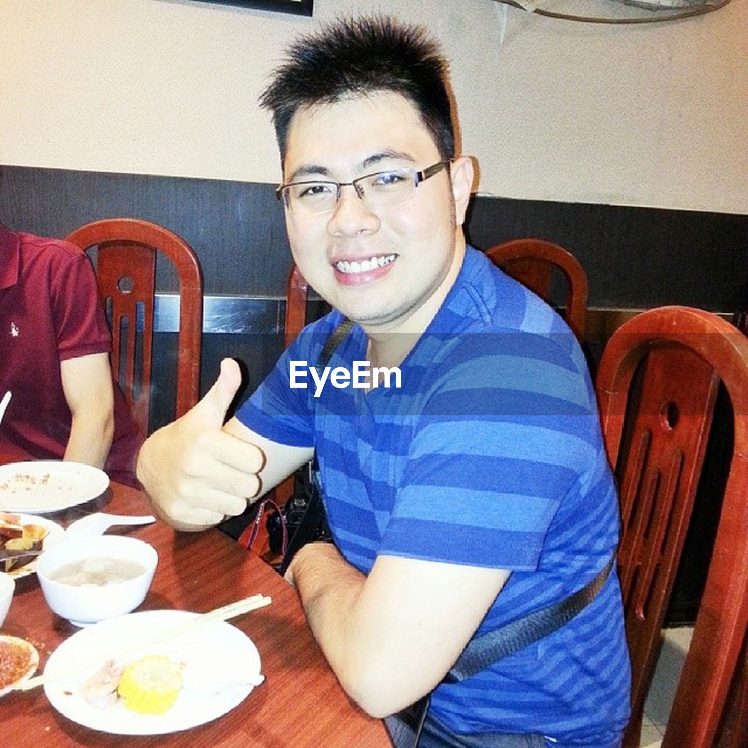 indoors, looking at camera, portrait, person, casual clothing, lifestyles, front view, food and drink, leisure activity, sitting, young adult, young men, smiling, waist up, table, restaurant, happiness, holding
