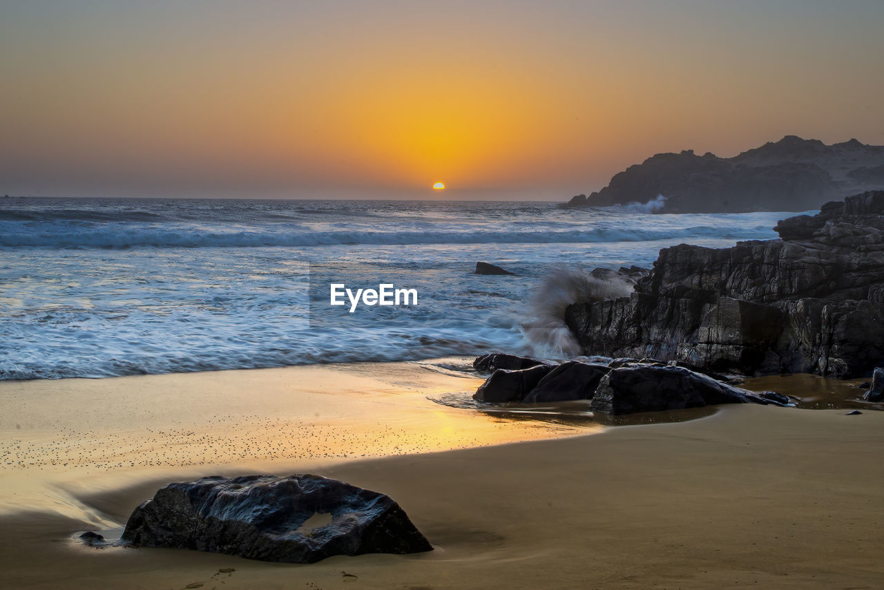sea, water, sky, land, beach, scenics - nature, sunset, horizon, horizon over water, beauty in nature, motion, rock, sand, wave, nature, orange color, rock - object, tranquil scene, no people, outdoors, power in nature