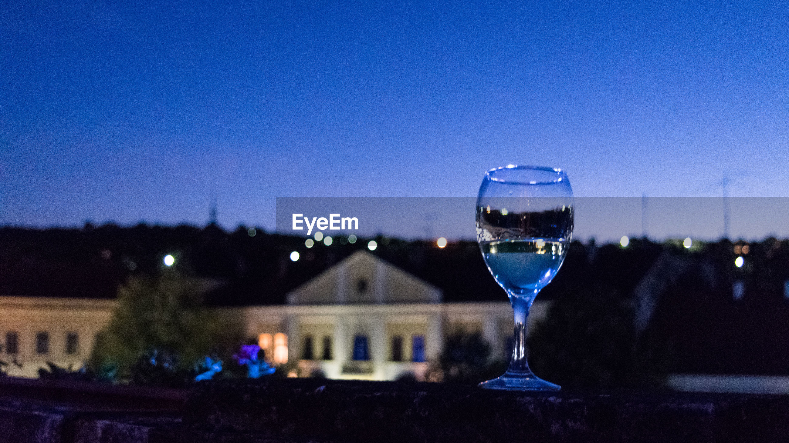 Close-up of wineglass against clear sky at night