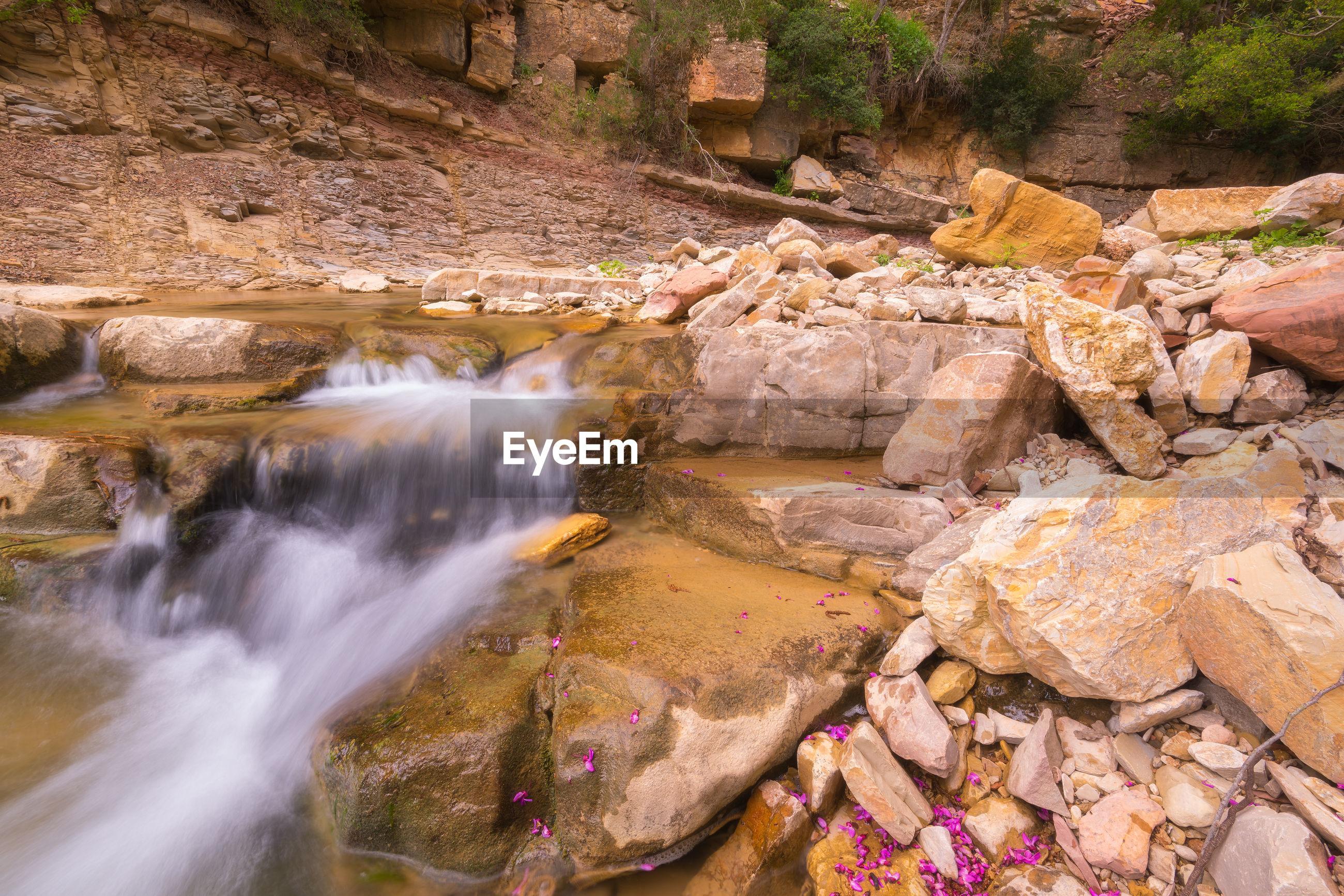 SCENIC VIEW OF WATERFALL ALONG ROCKS