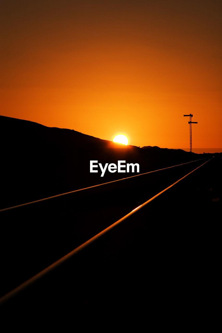 Railroad tracks on silhouette landscape against orange sky during sunset