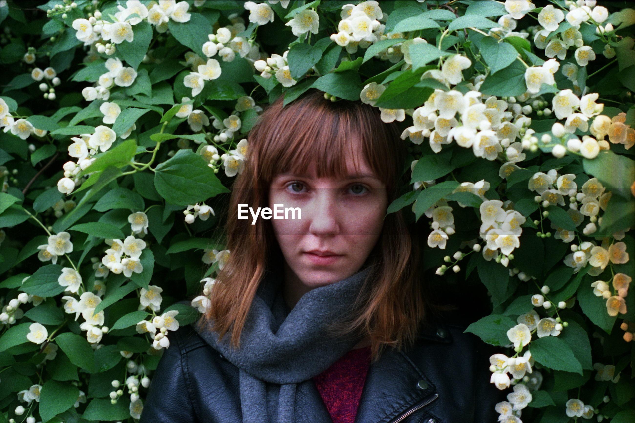 Close-up portrait of young woman amidst flower plants