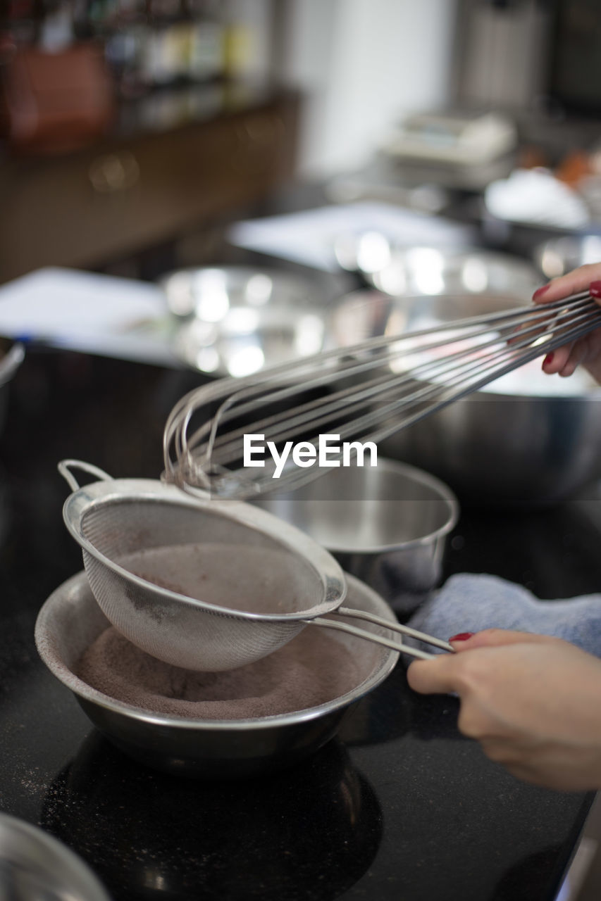 Cropped image of woman holding wire whisk while baking in kitchen