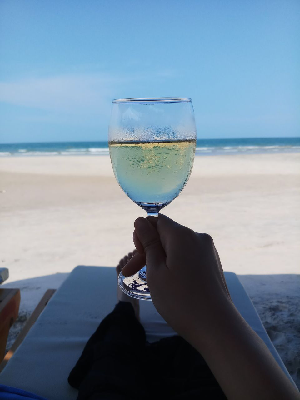 sea, beach, water, land, sky, human hand, one person, hand, nature, horizon over water, holding, glass, horizon, human body part, leisure activity, real people, lifestyles, scenics - nature, food and drink, outdoors