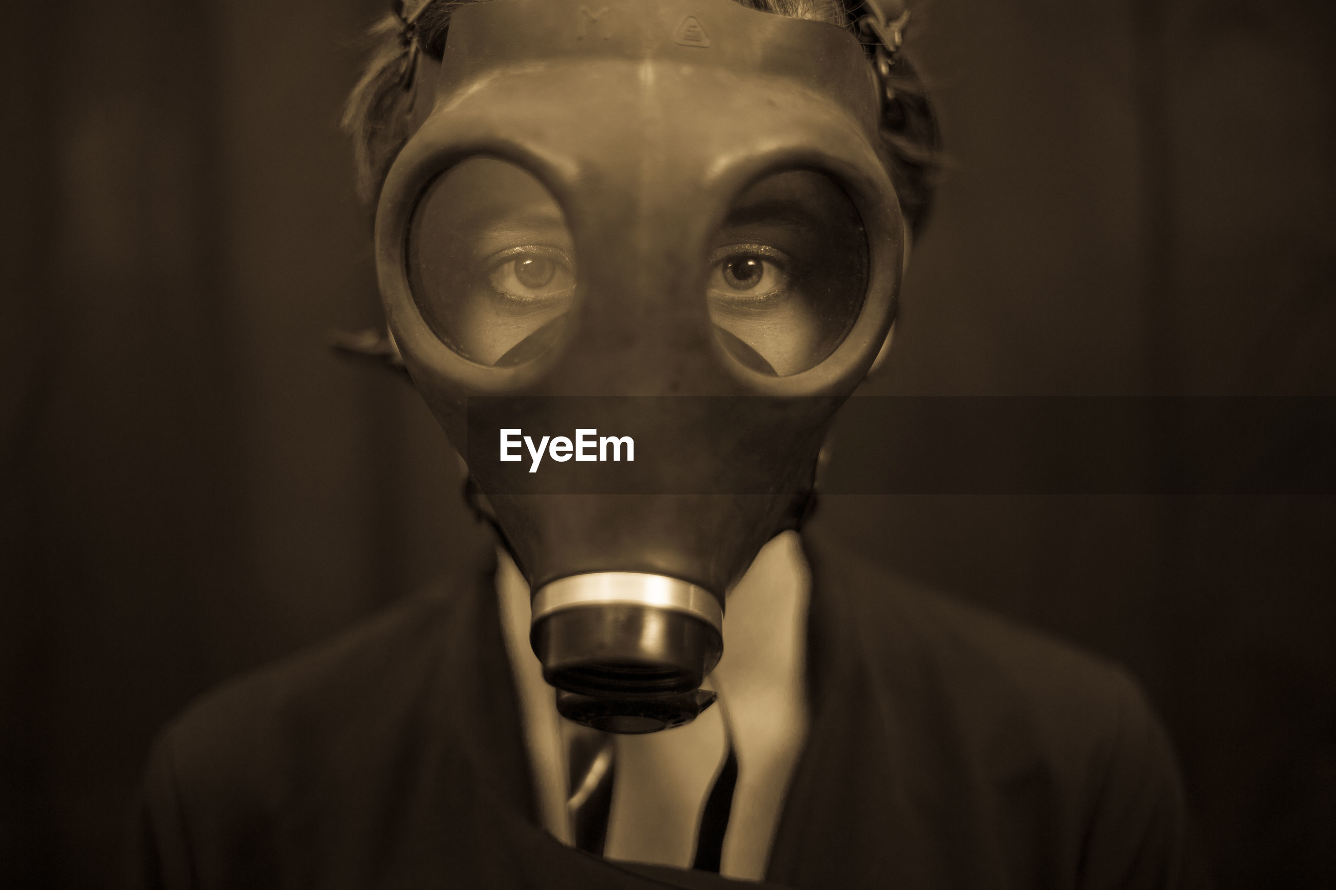 Close-up portrait of young woman wearing gas mask