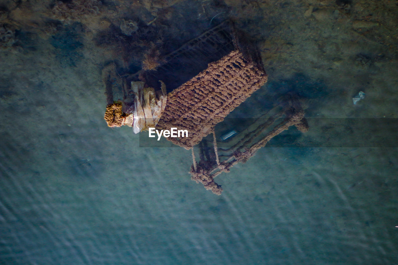 High angle view of abandoned shopping cart in sea