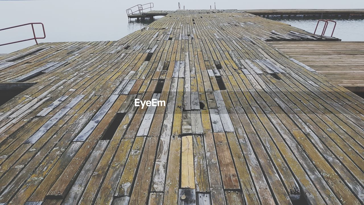 wood - material, water, no people, architecture, day, nature, outdoors, built structure, pattern, pier, sky, metal, industry, direction, the way forward, railing, boardwalk, sea, high angle view