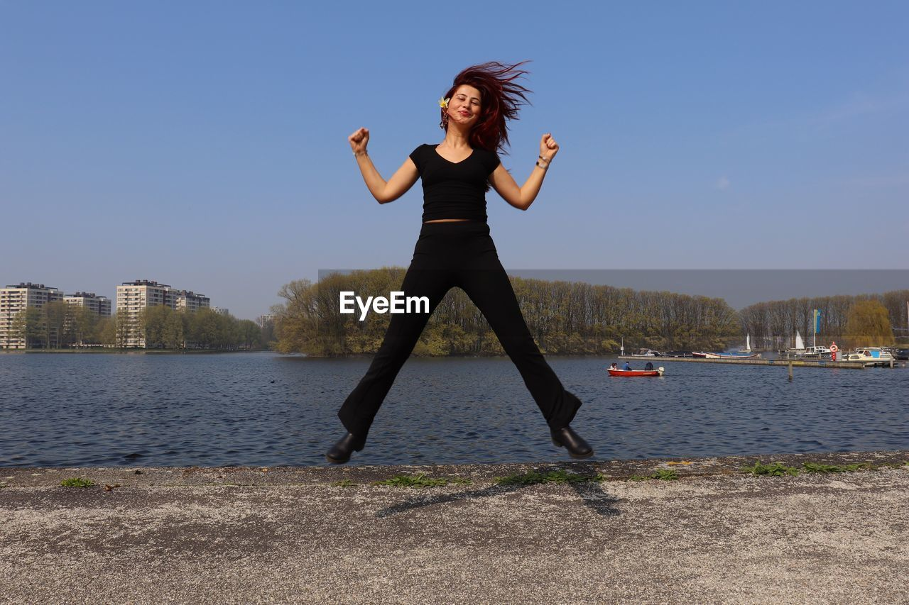 Full length portrait of young woman jumping against lake