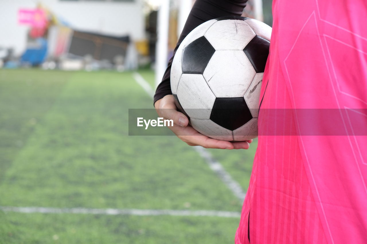 sport, soccer, team sport, ball, sports equipment, grass, soccer ball, one person, focus on foreground, soccer field, day, athlete, playing field, human body part, leisure activity, real people, playing, football, competition, outdoors