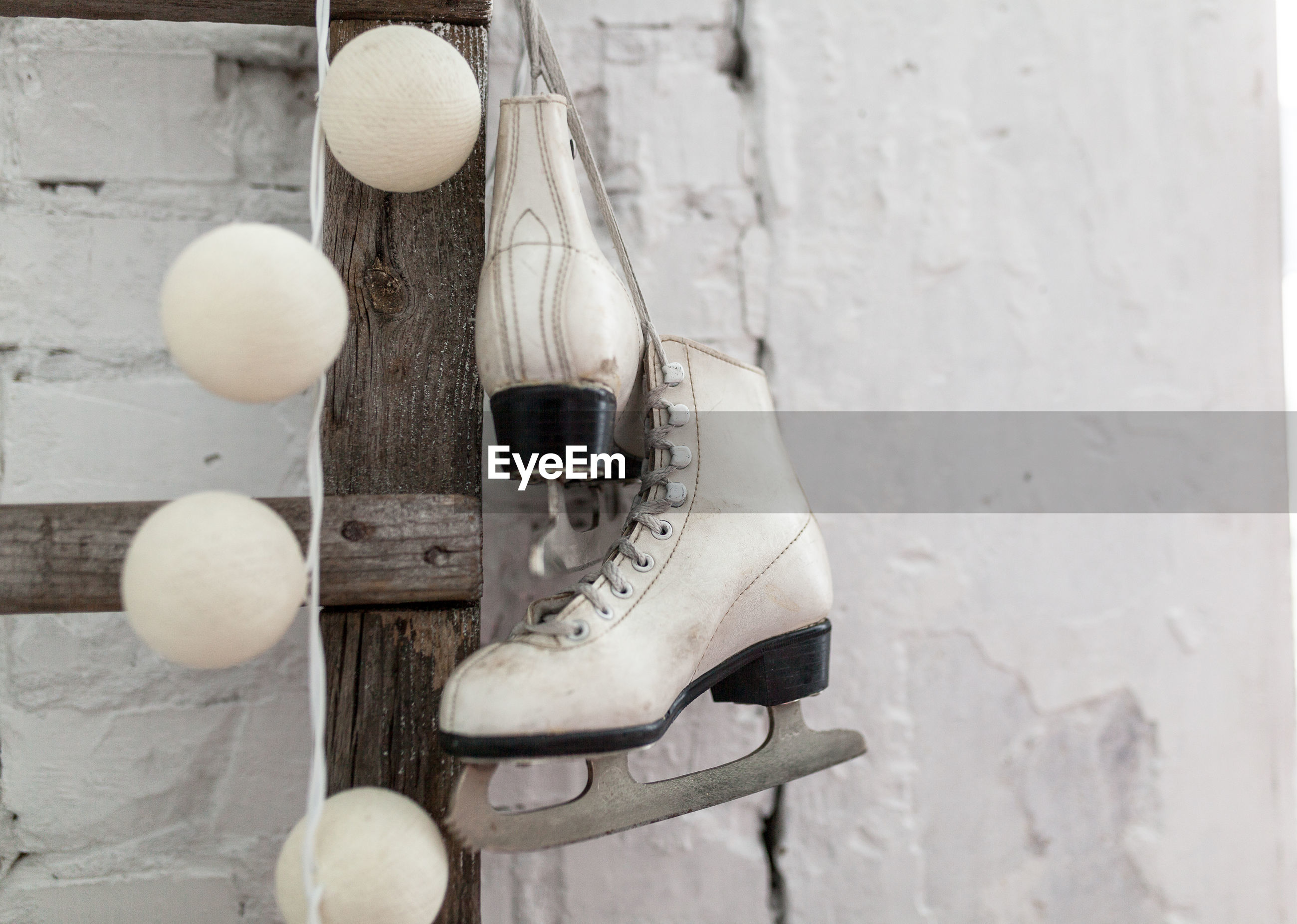 Close-up of ice skates hanging on ladder against wall