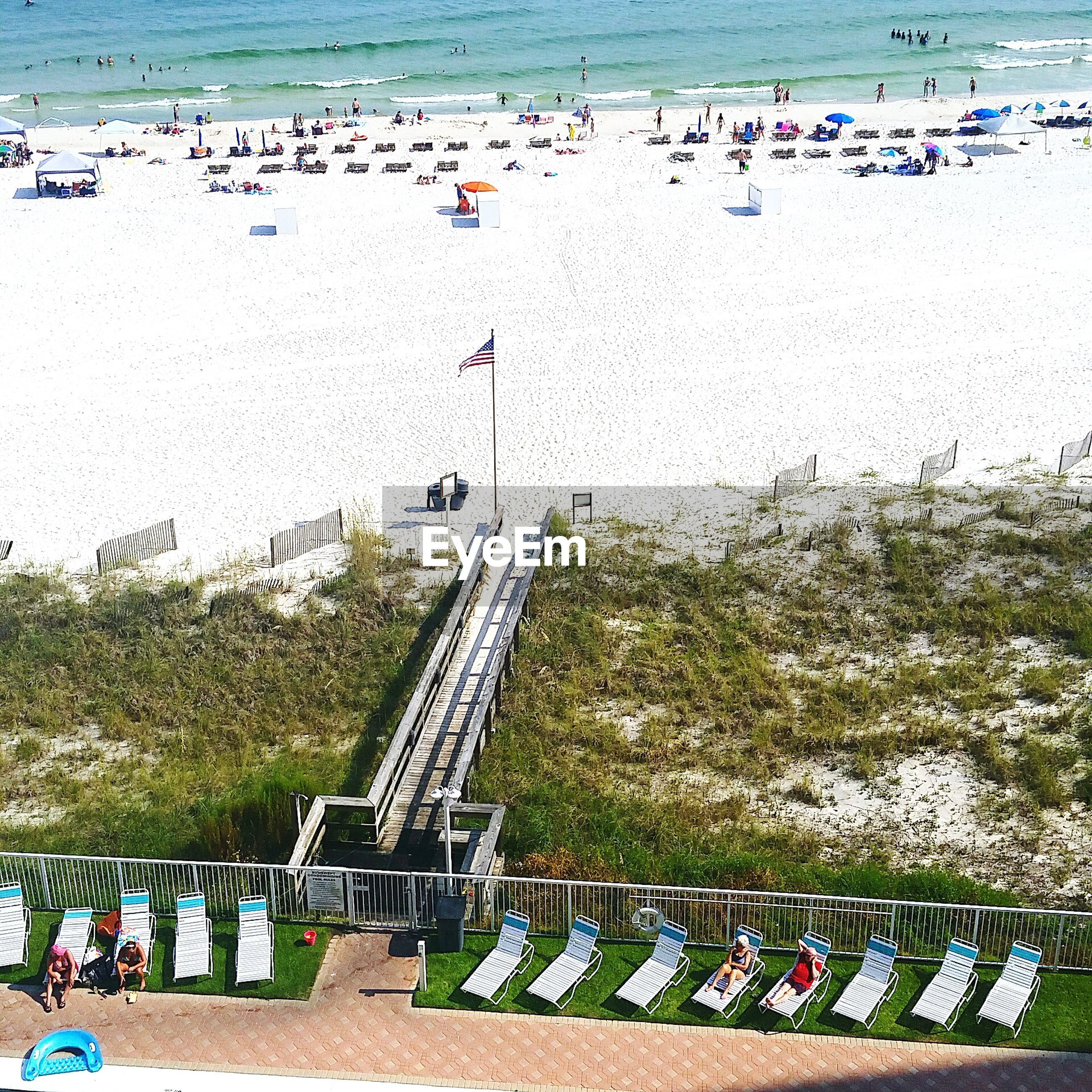 railing, large group of people, high angle view, built structure, tree, day, in a row, fence, architecture, beach, outdoors, water, incidental people, travel, steps, nature, travel destinations, safety, protection