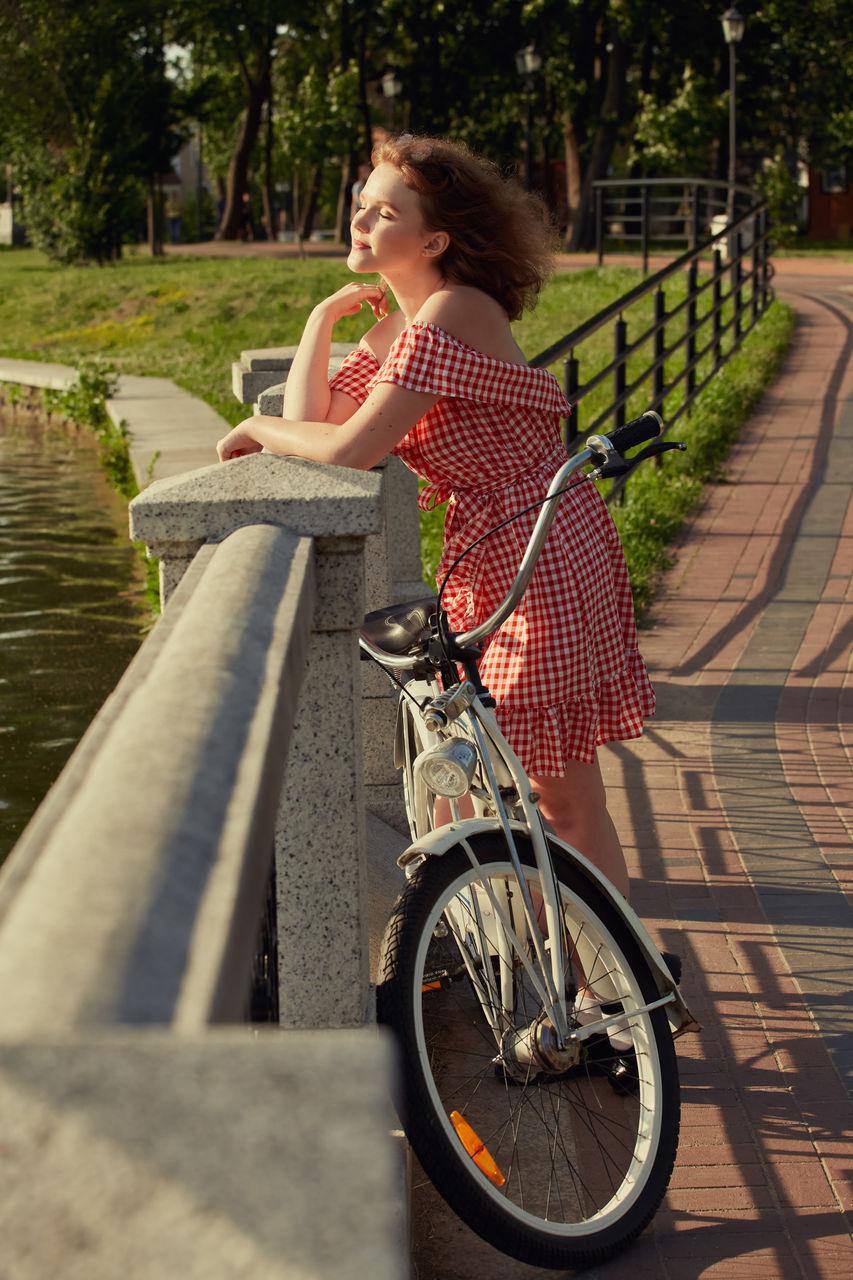 WOMAN RIDING BICYCLE SITTING ON SIDEWALK