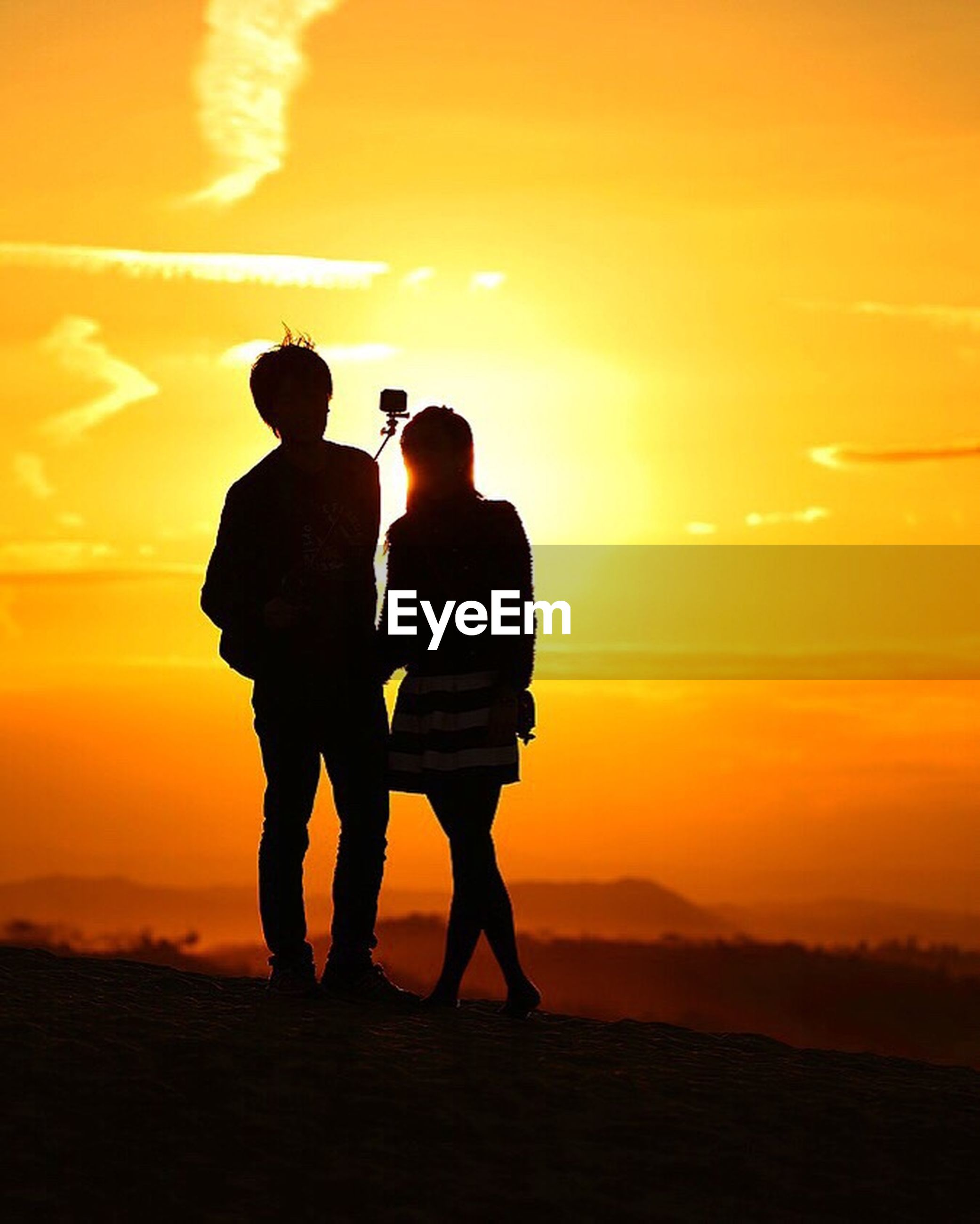 sunset, two people, silhouette, orange color, togetherness, heterosexual couple, love, sun, couple - relationship, full length, bonding, women, beauty in nature, men, leisure activity, nature, lifestyles, real people, sky, standing, friendship, vacations, adult, outdoors, young adult, young women, people, adults only