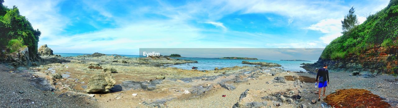 Panoramic View Of Rocky Shore By Sea Against Cloudy Sky