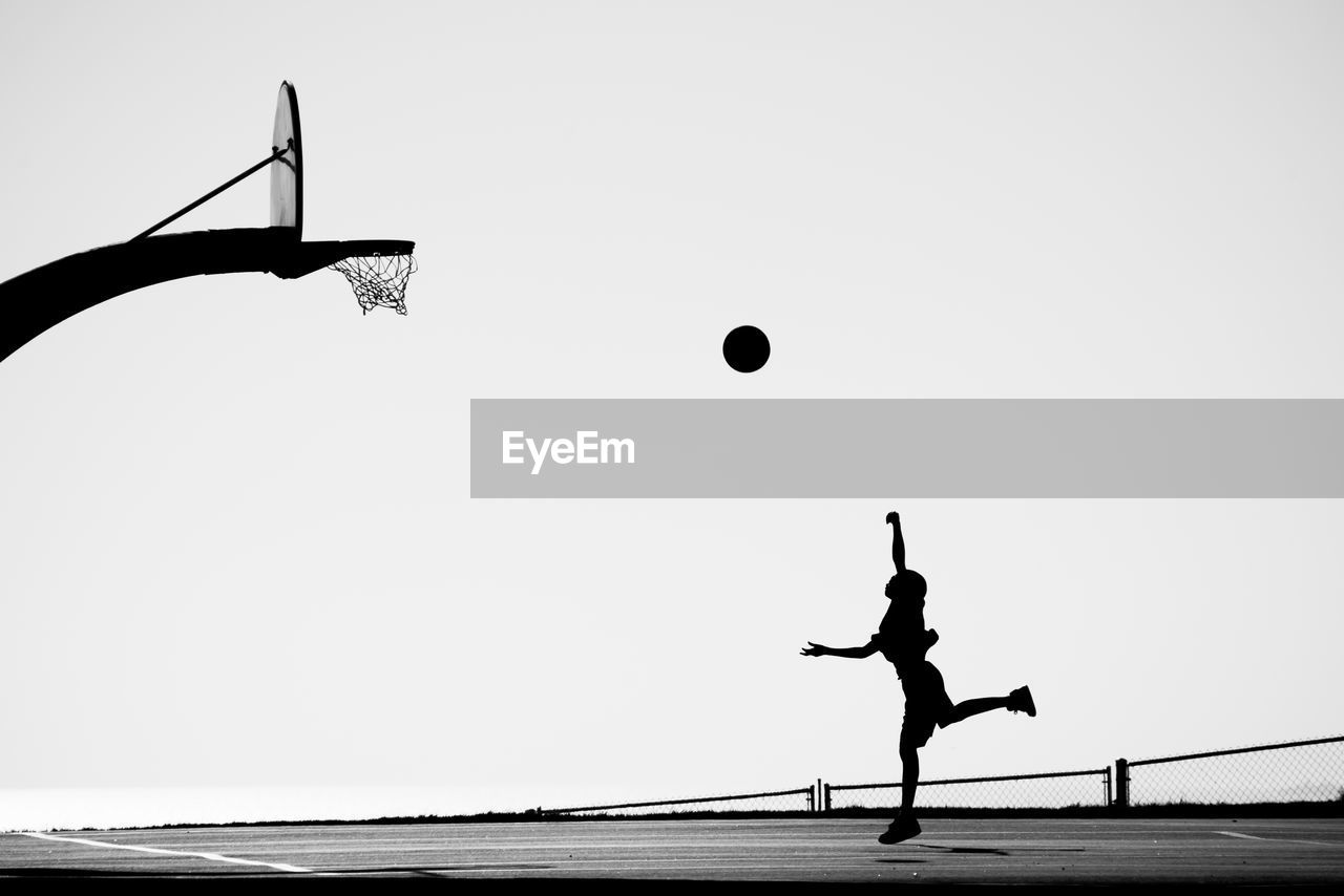 Silhouette Man Playing Basketball On Court Against Clear Sky