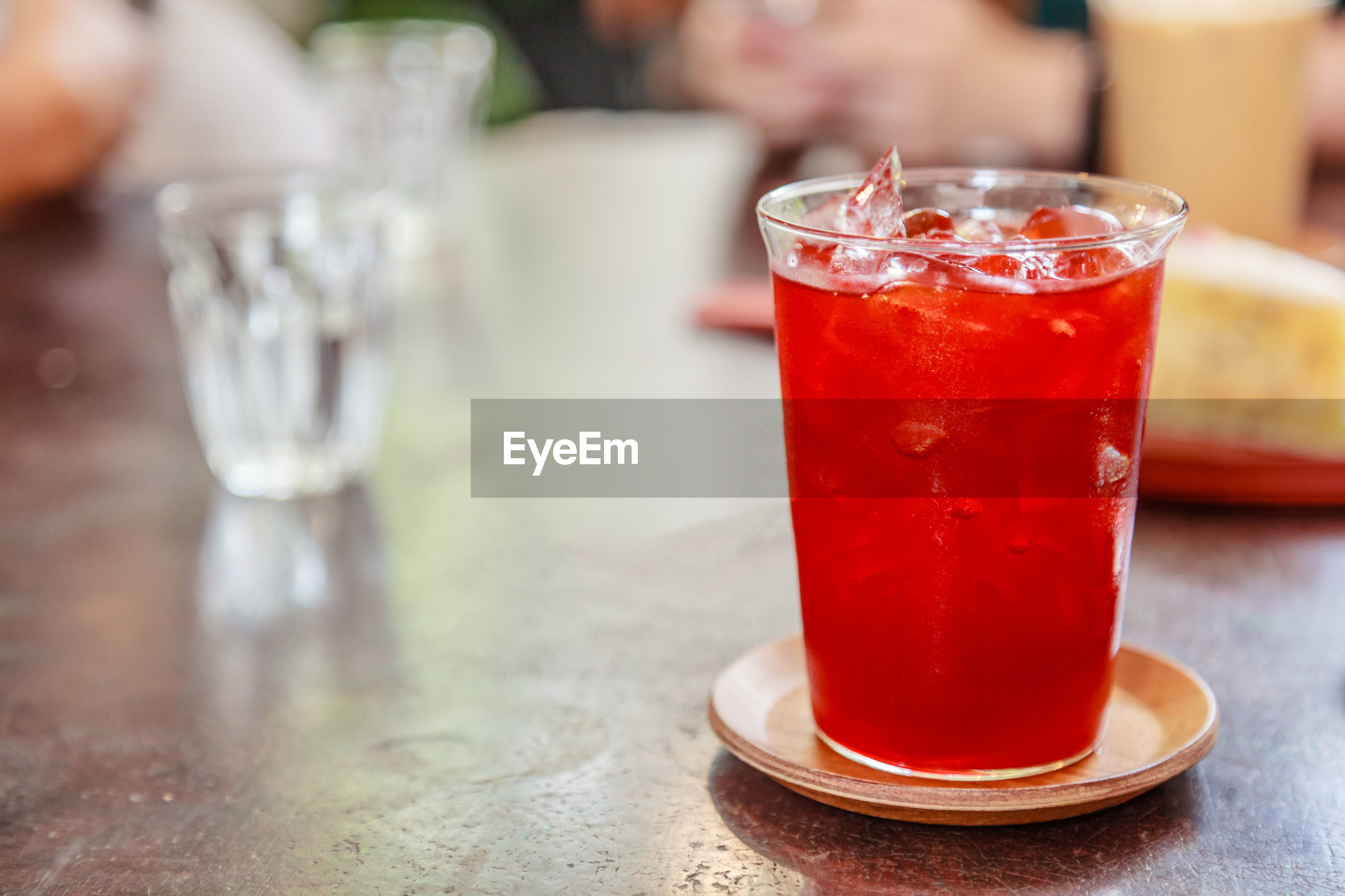 CLOSE-UP OF DRINK ON GLASS TABLE