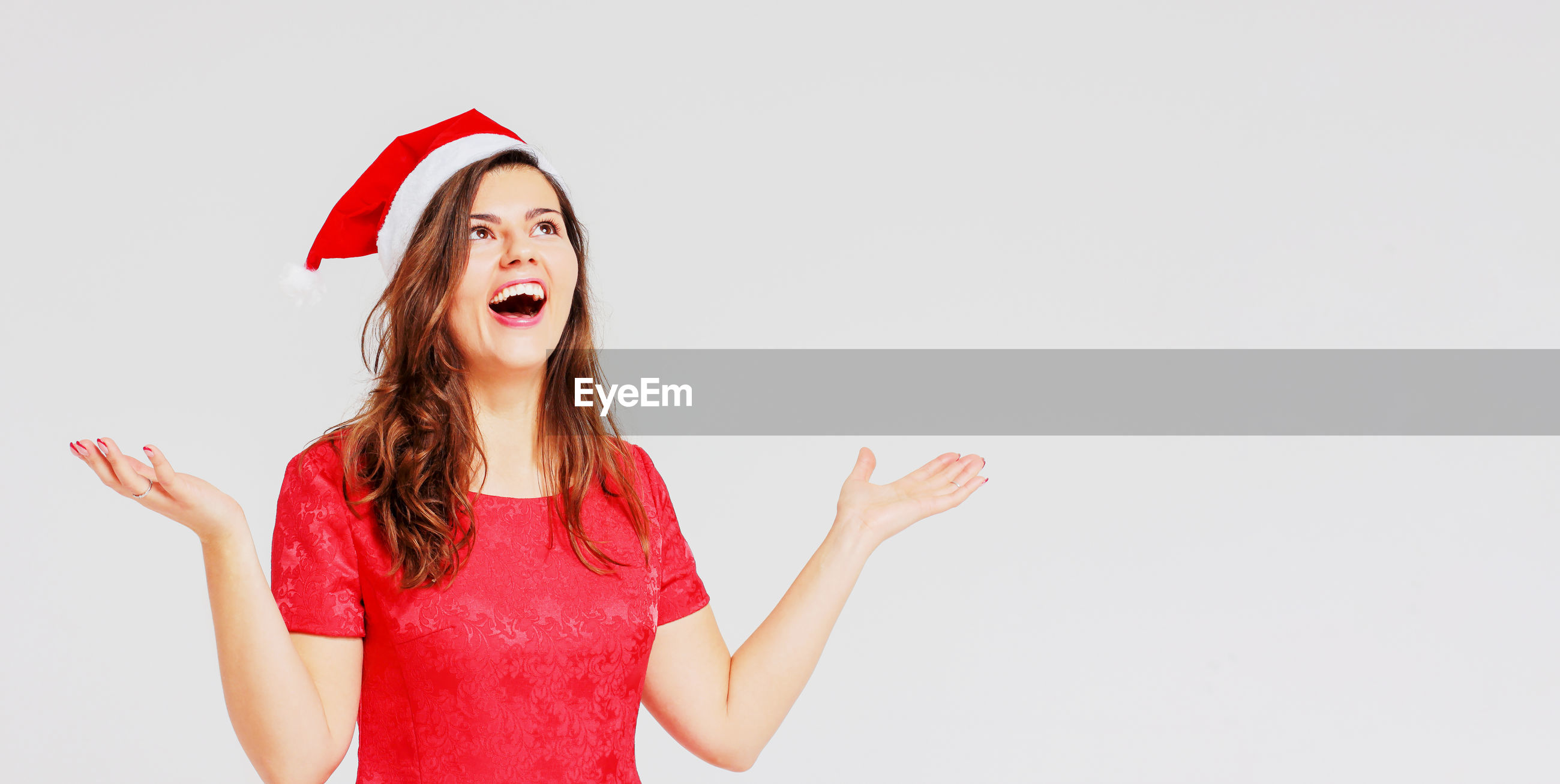 Amazed young woman wearing santa hat while standing against gray background