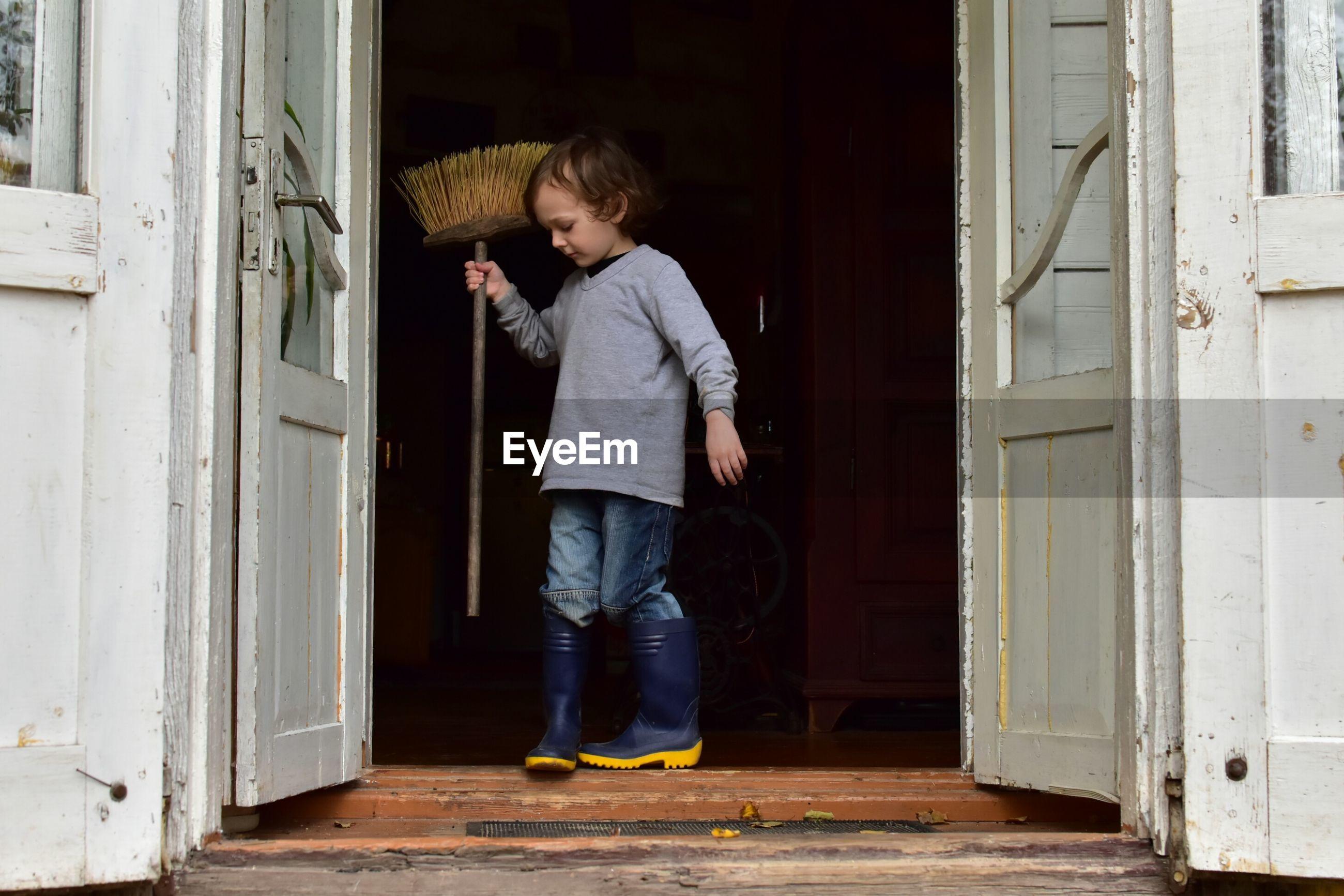 Full length of boy holding broom on doorway