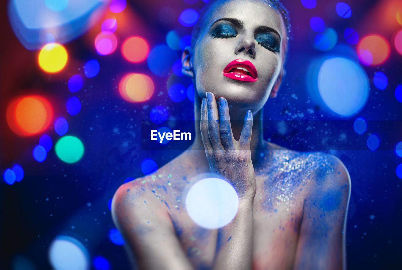 Seductive naked woman with glitter against blue background
