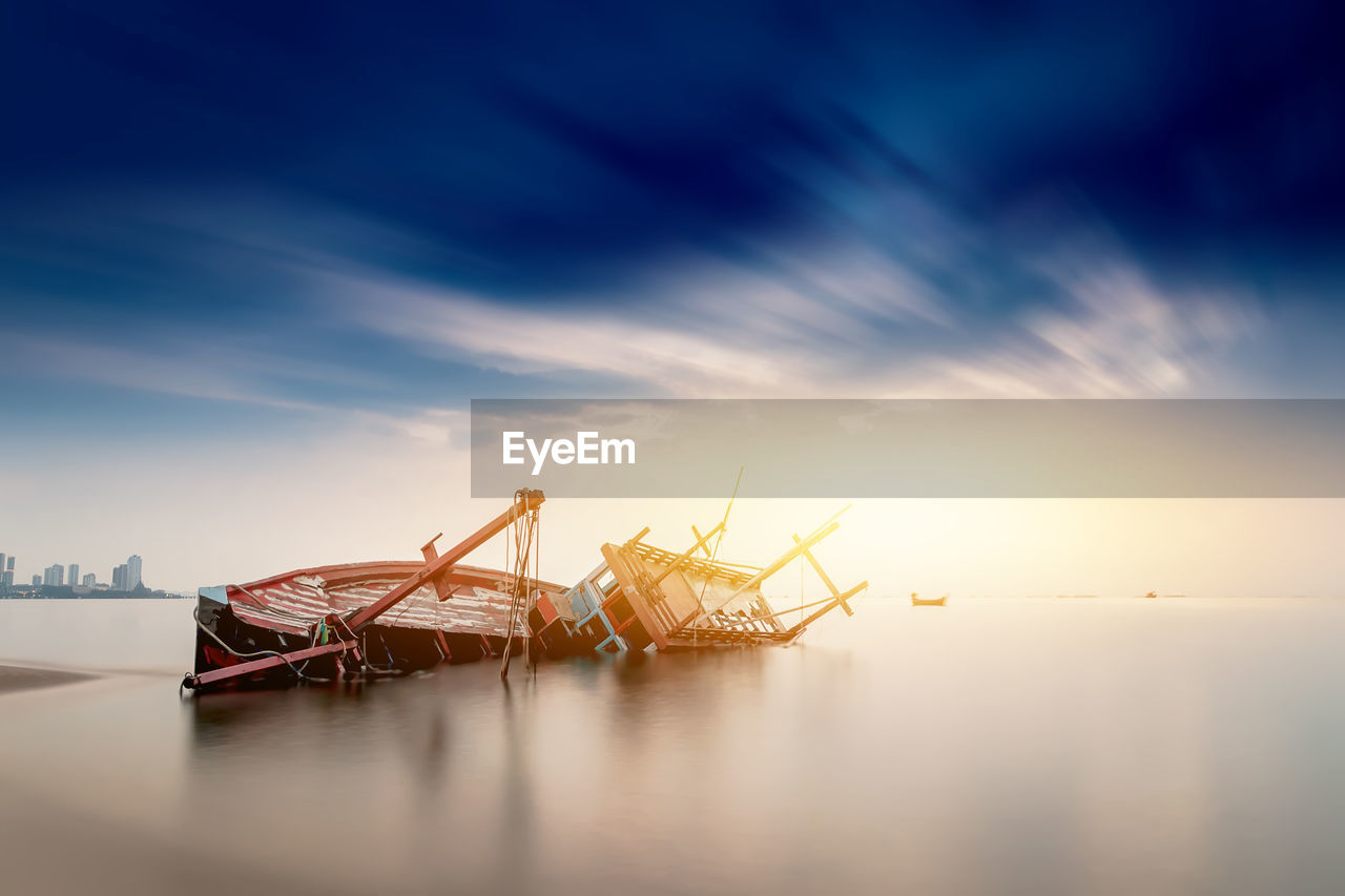 FISHING BOAT MOORED AT SEA AGAINST SKY