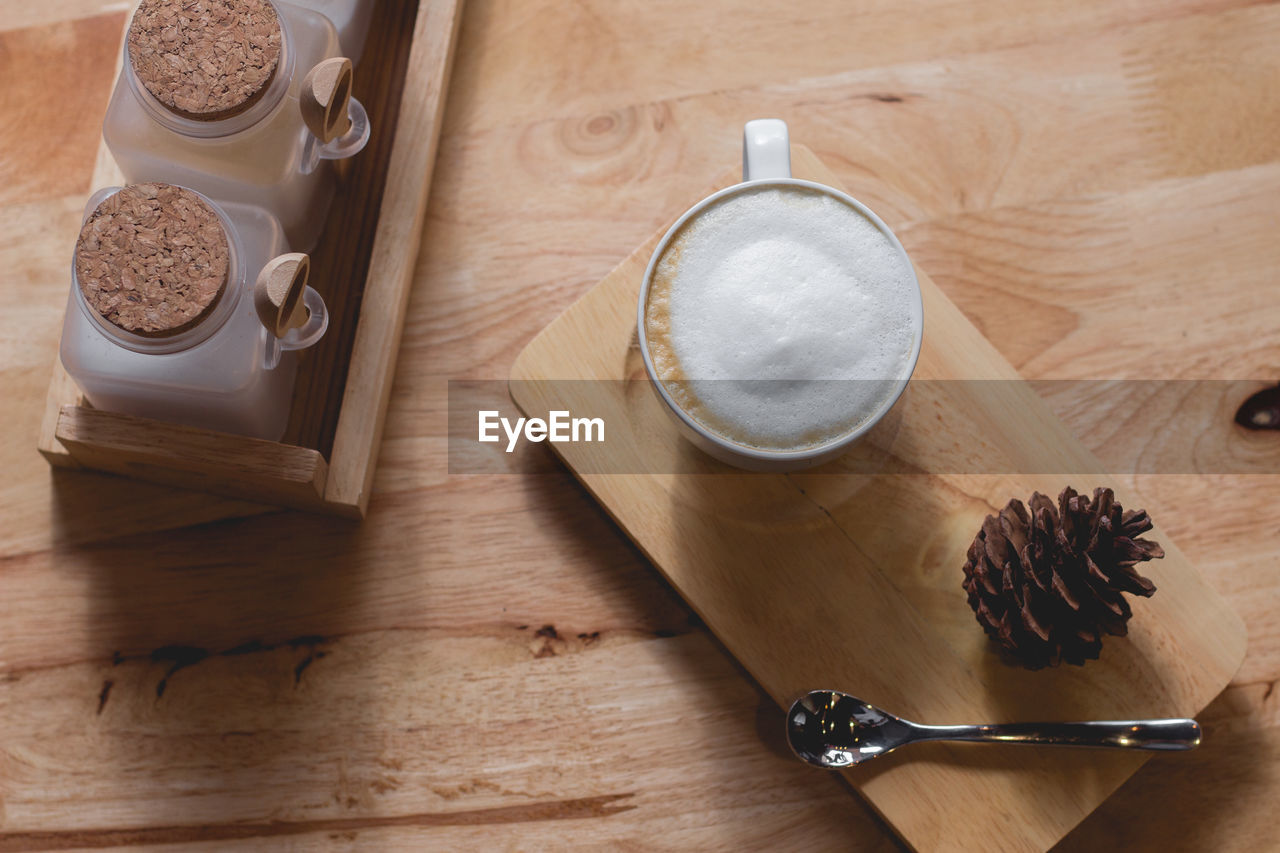 food and drink, table, still life, drink, freshness, food, refreshment, high angle view, indoors, wood - material, coffee - drink, coffee, kitchen utensil, no people, eating utensil, directly above, spoon, cup, coffee cup, mug, frothy drink, latte, glass, tray, breakfast