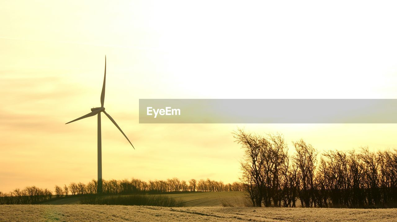 WIND TURBINES IN FIELD AGAINST SKY DURING SUNSET