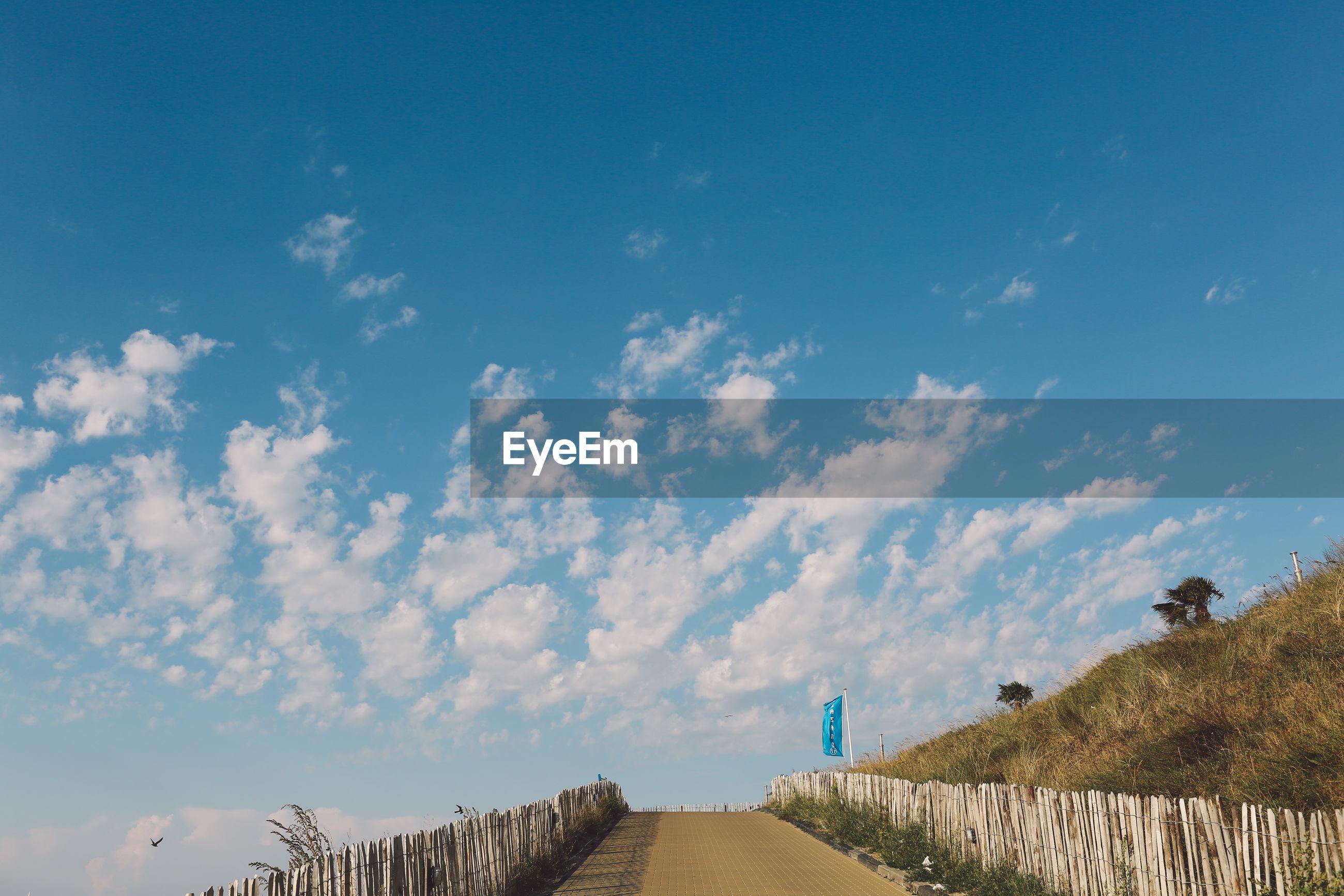 Empty walkway at beach against blue sky