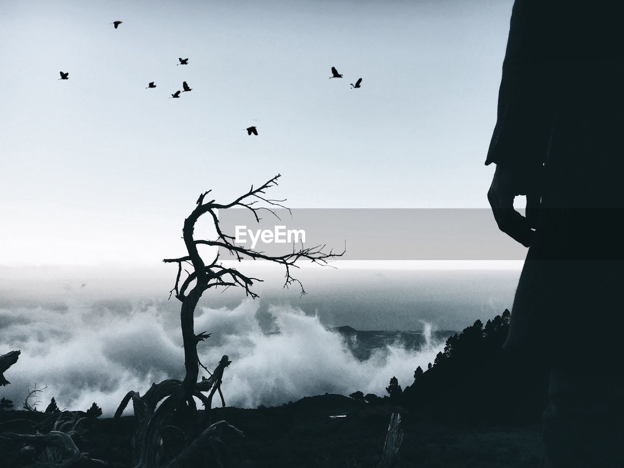 Low Section Of Silhouette Person Standing On Top Of Mountain