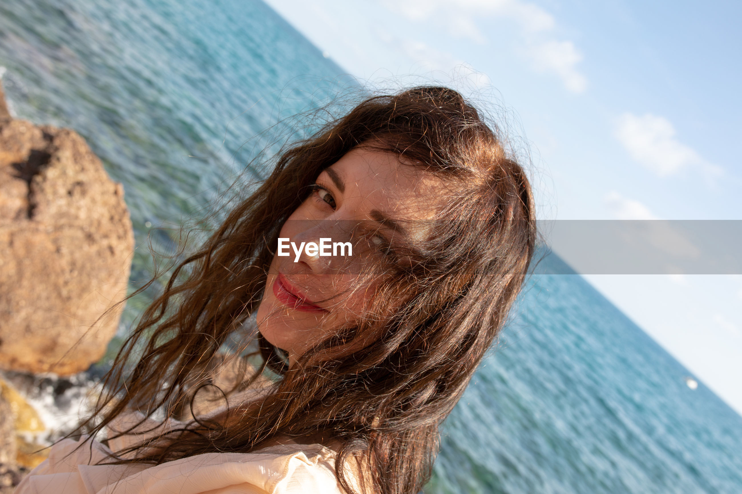 Close-up portrait of woman at beach against sky